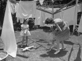 Suburban Mother Playing with Her Two Daughters While Hanging Laundry in Backyard Lámina fotográfica por Alfred Eisenstaedt
