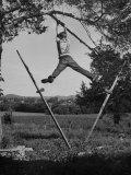 Kenneth Merriman Swinging on Tree Limb after Kicking Away Stilts Impressão fotográfica
