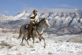 Cowboy On Grey Quarter Horse Trotting In The Snow At Flitner Ranch, Shell, Wyoming Reproduction photographique par Carol Walker