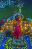 India, Varanasi Young Boy in Pink and Yellow Robes Holds Up an Offering to the Ganges River Impressão fotográfica por Ellen Clark