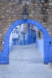 Morocco, Chefchaouen. a Blue Arch and Quiet Street Entering the Medina of the Village Fotografisk tryk af Brenda Tharp