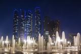 UAE, Abu Dhabi, Emirates Palace Hotel fountains and Etihad Towers, dusk Reproduction photographique par Walter Bibikw