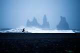 Tourist running on Black Sand Beach, Iceland, Polar Regions Fotoprint van John Alexander