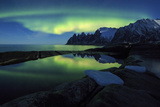The Northern Lights (aurora borealis) and stars reflected in the icy sea, Tungeneset, Senja, Troms  Photographic Print by Roberto Moiola