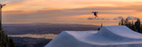 Freestyle skier doing a trick off a jump above city at sunset, Canada, North America Fotografie-Druck von Tyler Lillico