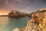 Pink sunrise on the turquoise sea framed by old town perched on the rocks, Polignano a Mare, Provin Photographic Print by Roberto Moiola