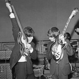 Paul Mccartney and George Harrison Tune their Guitars Foto von  Associated Newspapers