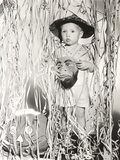 Little Boy in Halloween Costume Holding Mask Standing by Streamers Foto