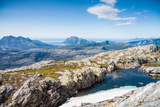 A Small Lake with Snow and View towards Mountains and the Sea in Northern Norway Fotografisk trykk av  Lamarinx