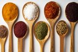 Spices in Wooden Spoons Isolated on White Background Valokuvavedos tekijänä Gecko Studio