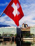 Swiss Flag on Mont Blanc Bridge with Quai General Guisan in Background, Geneva, Switzerland Fotografie-Druck von Witold Skrypczak