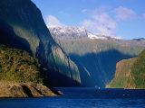 Boat in Distance Between Mountains, Milford Sound, New Zealand Fotografie-Druck von Peter Hendrie