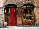 Bicicletta parcheggiata fuori da un negozio di alimentari storico a Siena, Toscana, Italia Stampa fotografica di John Elk III