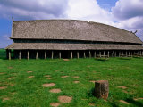 Longhouse in Stave Style at Viking Ring Fortress, Trelleborg, West Zealand, Denmark Fotografisk tryk af John Elk III