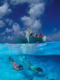 Female Divers Submerged Below Catamaran Photographic Print by Amos Nachoum