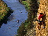 Man Climbing a Rock Wall above the River, Oregon Fotografisk tryk af Kate Thompson