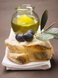 Olive Sprig with Black Olives on White Bread, Olive Oil Behind Fotografie-Druck