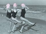 Three Women on Beach with Pink Towels on Head Fotoprint van Jim McGuire