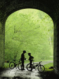 Two Silhouetted Cyclists Stop in a Tunnel on a Bike Trail Fotografisk trykk av Richard Nowitz