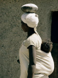 A Xhosa Woman Balances a Container on Her Head and a Baby on Her Back Fotografisk tryk af Walter Meayers Edwards