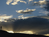 Silhouetted Figure Trail Running under a Cloud Filled Sky Fotografisk trykk av Bobby Model