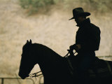 A Silhouette of a Rancher Riding a Horse Photographic Print by Dugald Bremner