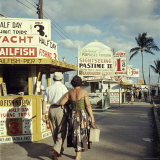 Vacationers Walking by Booths Advertising Boat Tours Lámina fotográfica por Hank Walker