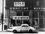 """Store Sign Reads, """"I am an American,"""" After Pearl Harbor Attack, and """"Sold"""", Following Evacuation Fotografisk tryk af Dorothea Lange"""