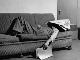 Writer Niven Busch Lying on Sofa with Newspaper over His Face as He Takes Nap from Screenwriting Fotografie-Druck von Paul Dorsey