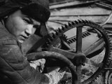 Russian Steel Worker Turning Gear Wheel in a Steel Mill Photographic Print by Margaret Bourke-White