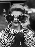 La mannequin June Pickney portant un manteau de fourrure en léopard et d'énormes lunettes de soleil bordées de fourrure de léopard Reproduction photographique par Stan Wayman