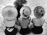 Models on Beach Wearing Different Designs of Straw Hats Fotografie-Druck von Nina Leen