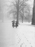 Snow Falling While People Take a Stroll Across Campus of Winchester College Fotografisk tryk af Cornell Capa