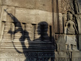 The Silhouetted Shadow of a Man Holding an Automatic Rifle is Cast against a Cambodian Temple Wall Fotografisk tryk af Paul Chesley