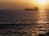 Cargo Ship at Sea Silhouetted at Sunset, Chile Fotoprint av Brent Winebrenner