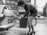 The Modern Female Petrol Pump Operator Refuelling a Car in Her Mini Skirt Reproduction photographique