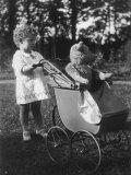 Little Girl Pushes Her Teddy Bear Around in a Pram Lámina fotográfica