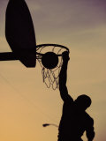 Silhouette of a Man Slam Dunking a Basketball Fotografisk tryk