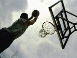 Low Angle View of a Man Shooting a Basket Reproduction photographique