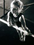 Girl Performing Gymnastics on Uneven Parallel Bars Impressão fotográfica