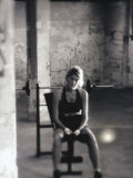 Young Woman Sitting on a Weight Bench Lámina fotográfica