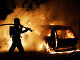 A Firefighter Extinguishes a Car in Les Musicians Fotografie-Druck