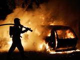 A Firefighter Extinguishes a Car in Les Musicians Lámina fotográfica