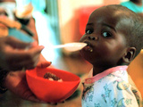An Unidentified Baby is Fed at a Home for Hiv/Aids and Abandoned Children Impressão fotográfica