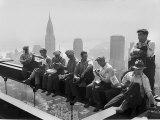 Rakennusmiehet lounastauolla teräspalkin päällä RCA-rakennuksen huipulla Rockefeller Centerissä Valokuvavedos