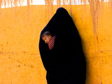 A Veiled Woman Carries Her Child Through the Streets of Erfoud Stampa fotografica