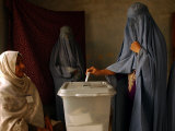 An Afghan Woman Wearing a Burqa Casts Her Ballot at a Polling Station Stampa fotografica