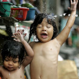 Filipino Children React as They Get a Shower Outside Their Homes Impressão fotográfica