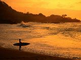 Surfer Standing at Waimea Bay at Sunset, Waimea, U.S.A. Photographic Print by Ann Cecil