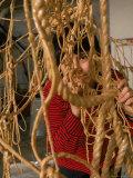 Eva Hesse Peering Through Her Sculpture of Rubber Dipped String and Rope Premium fototryk af Henry Groskinsky